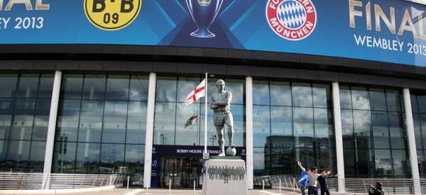 Fans pose in-front of the Bobby Moore Statue and Entrance on the day of the 2013 Champions League Cup Final.