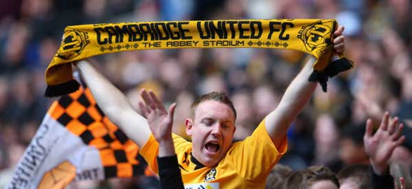 One Cambridge FC Fan holding a scarf and displaying the club's colours.