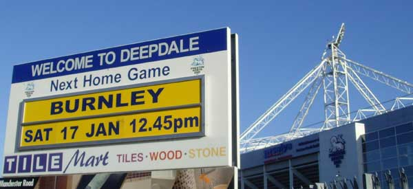 An artistic shot of Deepdale's Welcome sign and roof support in the distance.