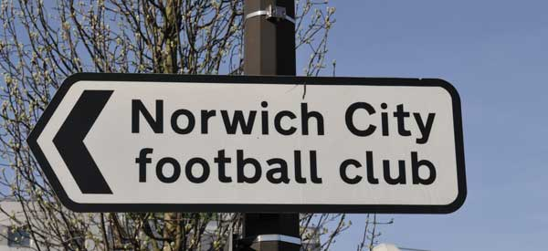A road sign depicting Norwich City Football Club is to the left.