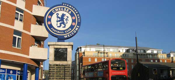 The Chelsea FC sign marking the entrance to Stamford Bridge. Of course it wouldn't be London without red buses.