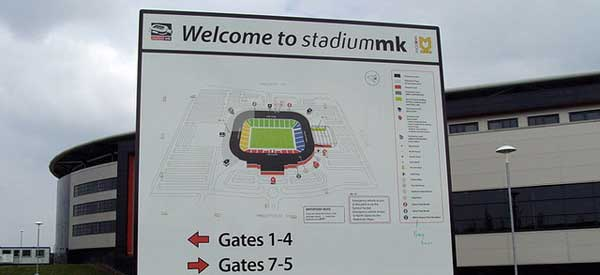 Welcome to Stadium MK visitors sign and map with the ground in the distance.